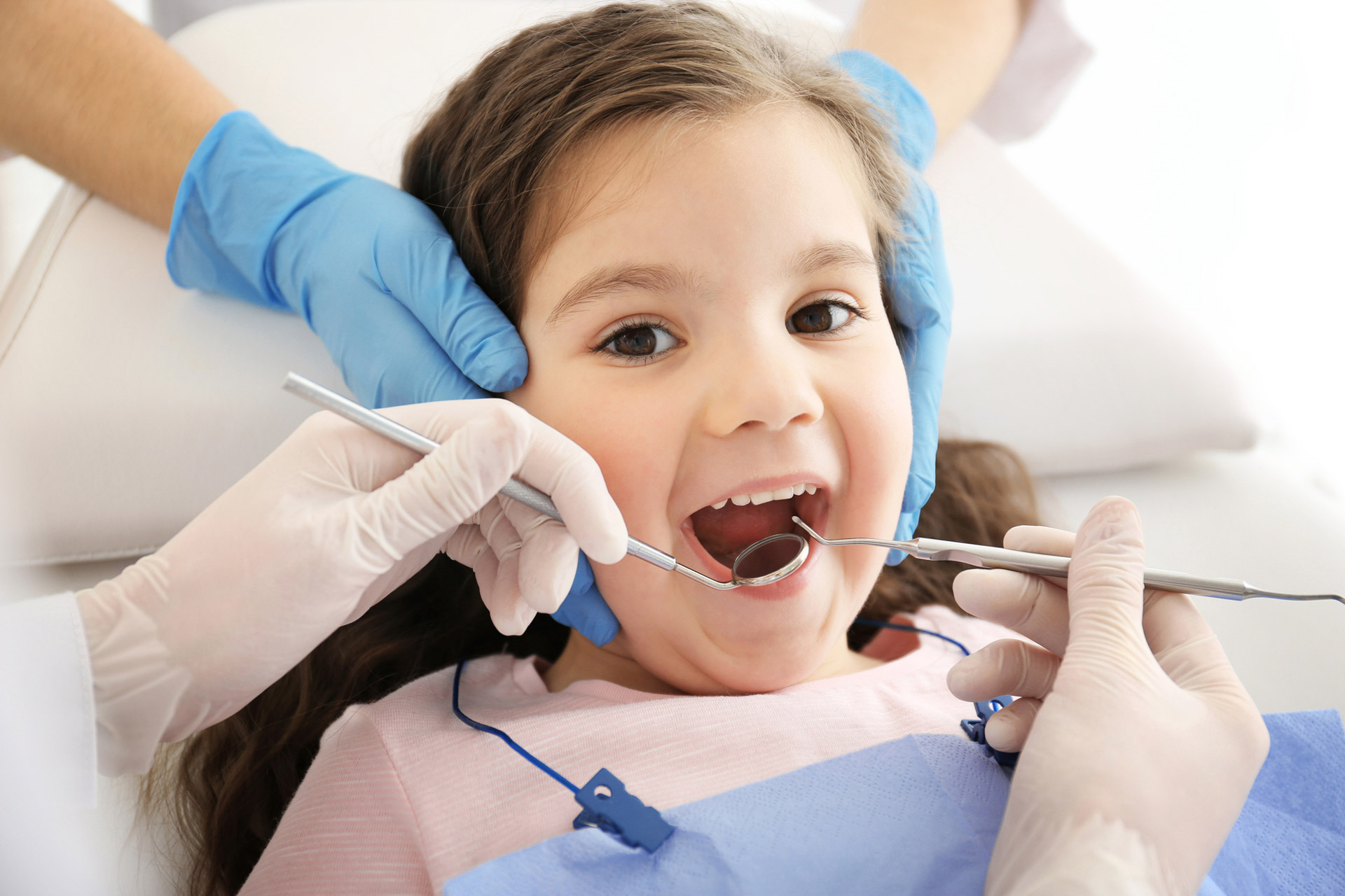 Dentist examining girl's teeth